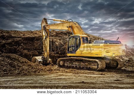 Excavator machinery at construction site cloudy sky in background.