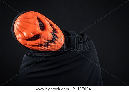 Mystery man with orange pumpkin evil mask on black background Halloween night costume concept