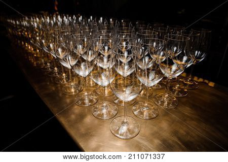 Large set of washed and clean transparent glasses arranged on the wooden table of bar or restaurant