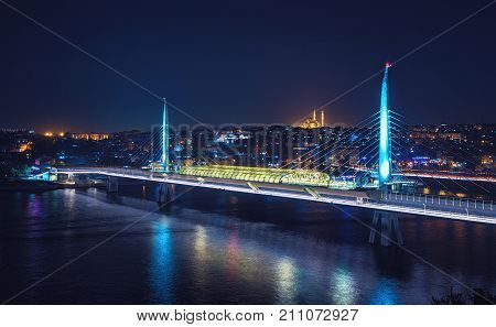 New Halic Metro Bridge view at night. Fatih mosque and Valenta Aqueduct on background. Halic Metro Bridge is in Golden Horn, Istanbul.