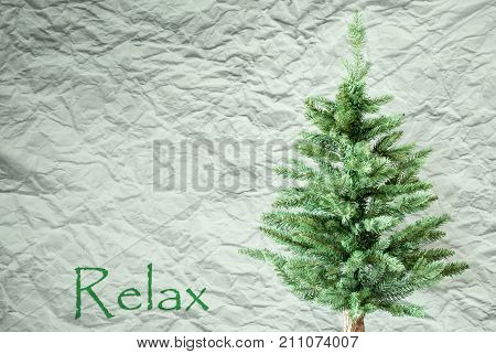 Crumpled Paper Background WIth English Text Relax. Christmas Tree Or Fir Tree In Front Of Textured Background.