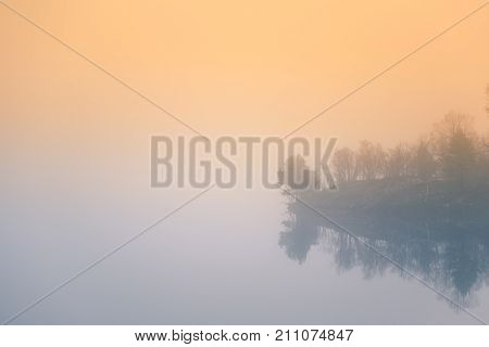 A beautiful colorful misty morning in Norway at the lake. Tree reflections in the water. Misty autumn landscape. Calm nordic scenery.