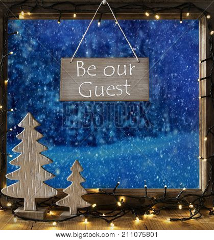 Sign With English Text Be Our Guest. Window Frame With Winter Landscape With Snow. View To Snowy Trees Outside With Snowflakes. Christmas Tree And Fairy Lights.