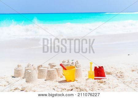 Sandcastle at white beach with plastic kids toys