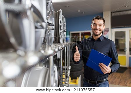 business, maintenance and people concept - male manager with alloy wheel rims and clipboard showing thumbs up at car repair service or auto store
