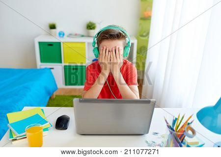technology, gaming, cyberbullying and people concept - upset boy in headphones with laptop computer at home lost video game or suffer of bullying