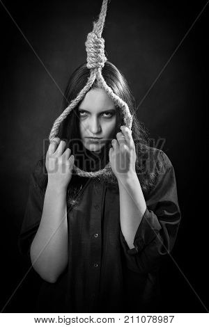 sad young woman with noose on dark background looking at camera