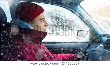 A man in winter clothes drives a car in winter
