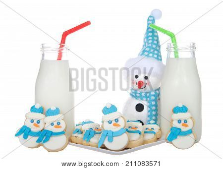 Snowmen sugar cookies with blue scarfs and fluffy blue and white hats on a plate with bottles of milk green and red straws. More snowmen cookies standing next to glasses of milk