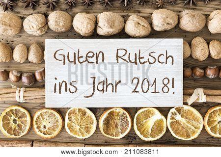 Sign With German Text Guten Rutsch Ins Jahr 2018 Means Happy New Year 2018. Christmas Food Flat Lay With Walnut, Hazelnut, Cinnamon Sticks And Orange Peel. Brown Wooden Background
