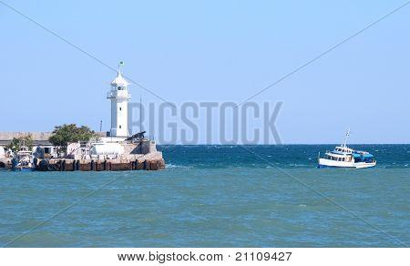 Small Beacon In A Sea Gulf And A Boat In The Sea