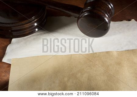 Judicial wooden hammer and old documents on the table