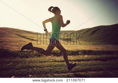 young fitness woman runner running on sunset grassland trail