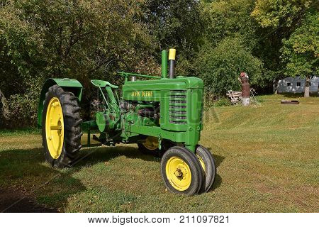 MOORHEAD, MINNESOTA, September 20, 2017: The restored old John Deere tractor with non-stock fenders is a product of John Deere Co, an American corporation that manufactures agricultural, construction, forestry machinery, diesel engines, and drivetrains.