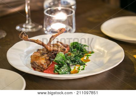 Grilled pigeon on white dish at luxury fine dining restaurant
