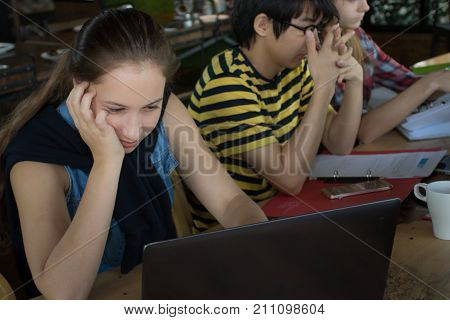 Group of teenage friends working and meeting in team with reports and laptop on wooden table/Selective focus Bored girl