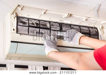 Technician Pointing To Air Conditioner Filter Full Of Trapped Dust