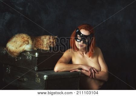 Young beautiful woman in a cat mask and an orange cat