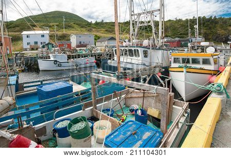Commercial Fishing Dock in Newfoundland:  Boats loaded with fishing gear wait at a concrete dock in a channel harbor on the west coast of Newfoundland.