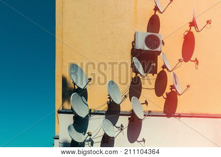 Satellite Dish Antennas On The House Fasade Wall. Television Communication Concept
