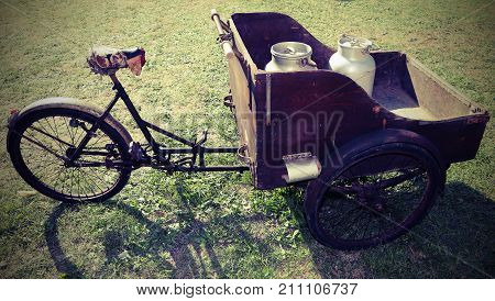 ancient wooden cart with old bicycle to transport the milk just leavened from the farm to the dairy with vintage effect