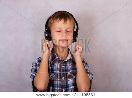 European boy listening to music on headphones eyes closed