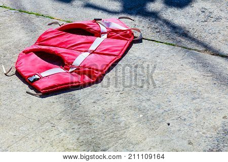 Life jacket lying on gray concrete floor ground drying out. Marine objects