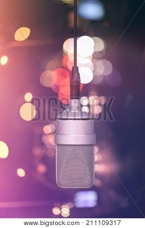 Professional Microphone Hanging On The Cable, Mic. Background Defocused Colors