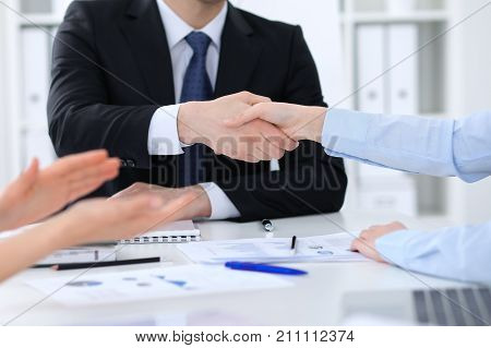 Unknown business people shaking hands, finishing up a meeting, close-up