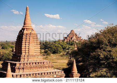A brick temple at sundown with the enormous Dhammayangyi temple in the background as seen from the Shwesandaw pagoda Bagan Myanmar poster