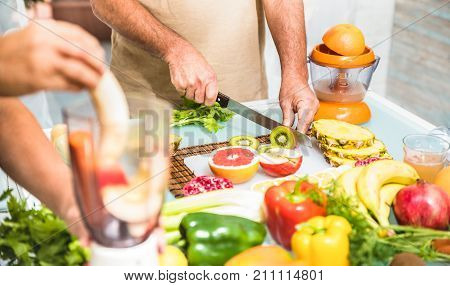 Detail of senior couple in kitchen with healthy food - Retired people cooking at home preparing blended centrifuge smoothie with bio fruit and vegetables - Happy elderly concept with mature pensioner
