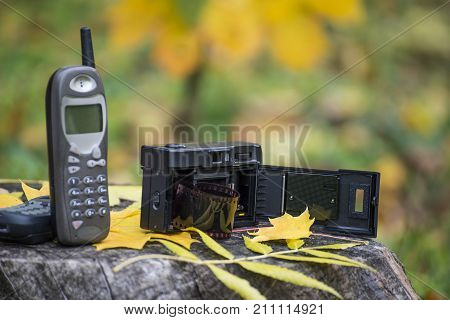 Old cellular phone and film camera. Mobile telephone from 90's and camera from 80's