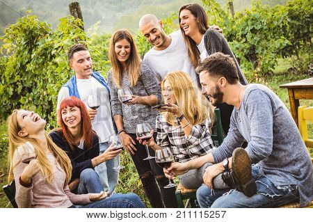 Happy friends having fun outdoor - Young people drinking red wine at harvest time in farmhouse vineyard winery - Youth friendship concept with mates using smartphone for a live mobile phone call