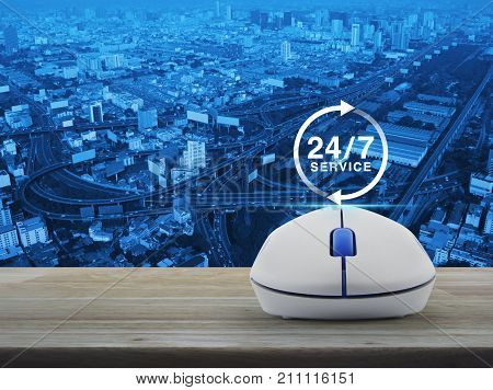 24 hours service icon with wireless computer mouse on wooden table over city tower street and expressway Full time service concept