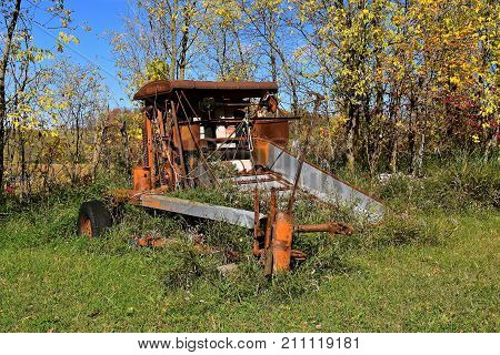 PEICAN RAPIDS, October 3, 2017: The old  orange baler surrounded by the autumn colored leaves and weeds is an from the company of Allis Chalmers, a manufacturer of machinery for various industries including agricultural and construction equipment.