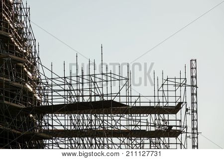 silhouette of scaffolding, working day at building construction, profile sunset light structure of scaffolding and cranes