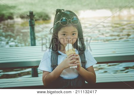 Asian little cute girl sitiing on wooden bench and eating ice cream at the park in vintage style.