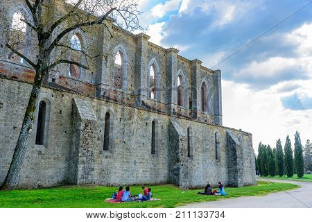 A Family Eat And Have Fun In The Meadow Next The Abbey Of San Galgano In Chiusdino.