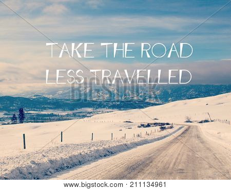 Winter landscape with snow covered isolated road in foreground. Mountains and forest in background. White text: Take the road less travelled.