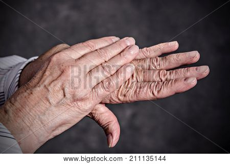 wrinkly hands of elderly woman in front of dark background