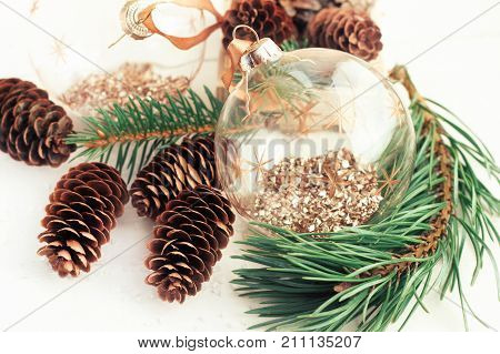 Preparing holiday decor. Minimalist Christmas tree balls with natural spruce cones and pine tree branches, close-up.
