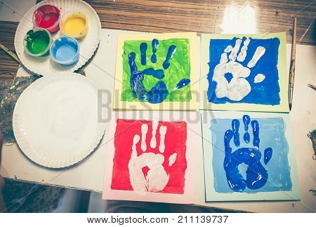 Top view collection of finger prints on art class. Colored hand print of watercolor on artwork. Pop art style. Strengthen the imagination of child for learning and education concepts. Vintage film filter effect.