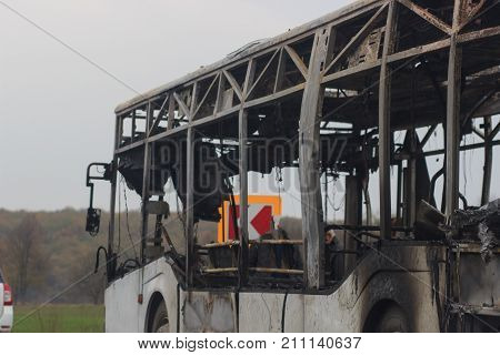 Burnt bus is seen on the street after caught in fire during travel, after fire.