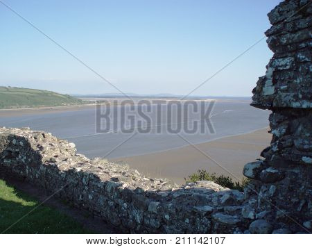 Norman castle wall overlooking a river estuary in Wales