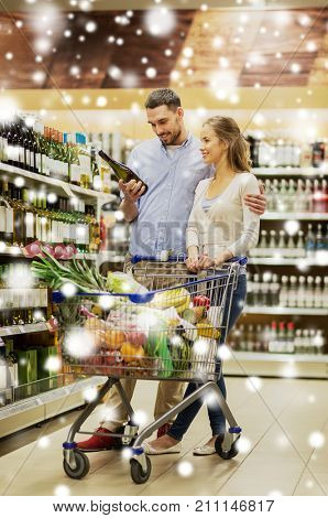 sale, consumerism and people concept - happy couple with bottle of non-alcoholic white wine and food in shopping cart at liquor store or supermarket over snow