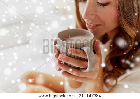 winter, cosiness, leisure and people concept - close up of happy young woman with cup of coffee or cacao over snow