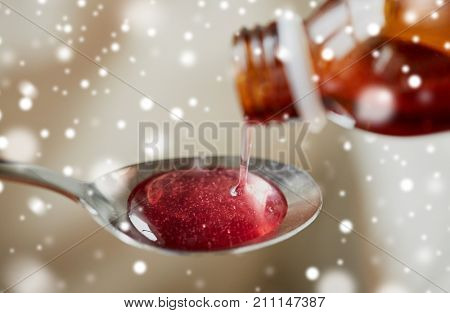 healthcare, treatment and medicine concept - bottle of medication or antipyretic syrup and spoon over snow