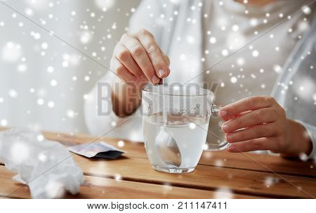 healthcare, medicine and people concept - close up of ill woman stirring medication in cup with spoon over snow
