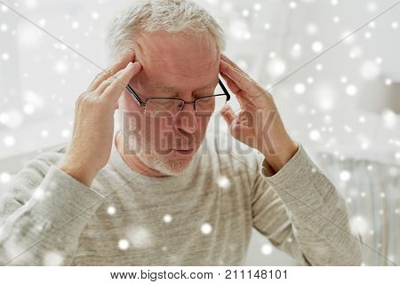 health, pain, stress and people concept - senior man suffering from headache at home over snow