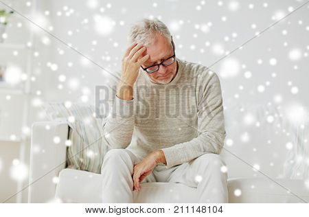 stress, old age and people concept - senior man suffering from headache at home over snow
